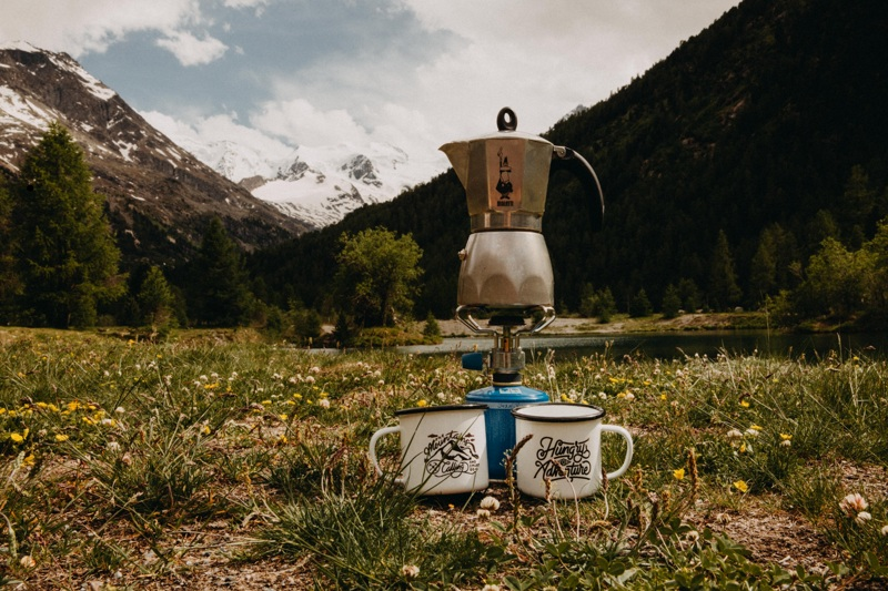 A photo of a moka pot in front of a beautiful mountain scenery.