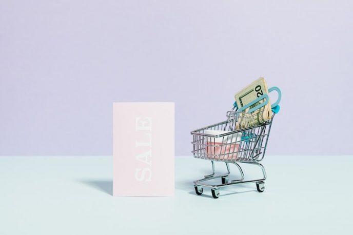 Ein Einkaufswagen mit Geld, daneben ist ein Sale-Schild.