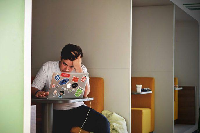 Un hombre estresado sentado frente a un ordenador en una cafetería. Preparar tu negocio de Afiliado para la temporada de ofertas puede ser duro debido a la presión por generar ingresos