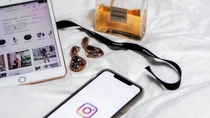 Dva chytré telefony na posteli, vedle nich jsou náušnice a lahvička parfému