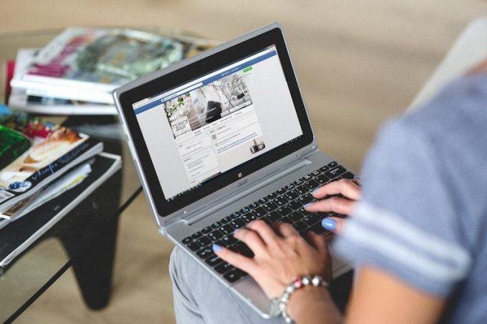 Žena píše na notebooku a upravuje svůj profil na Facebooku