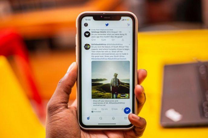 Muž drží chytrý telefon, na kterém je zobrazen informační kanál Twitteru