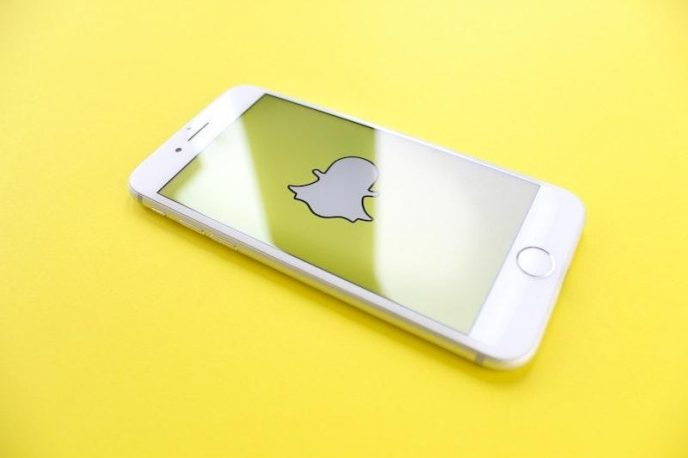 Chytrý telefon na žlutém podkladu, zobrazena je ikona Snapchatu