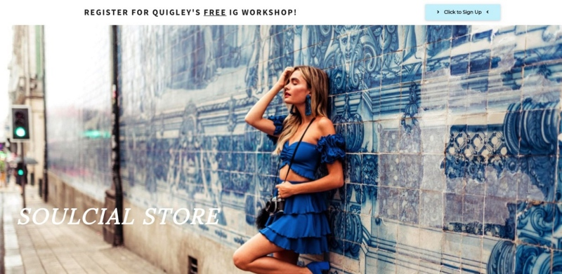 Young woman with blue dress posing in front of a wall. Fashion blogging example of how to pose solo.