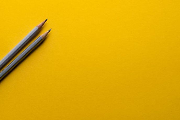 Två pennor på gult papper. Att skapa en innehållskalender är en väsentlig del av alla bloggares innehållsstrategi.