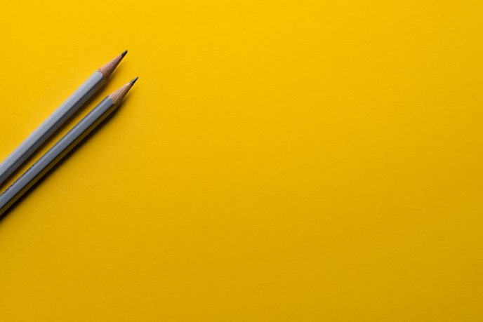 Twee potloden op geel papier. Het opstellen van een contentkalender is een essentieel onderdeel van elke goede contentstrategie voor bloggers.